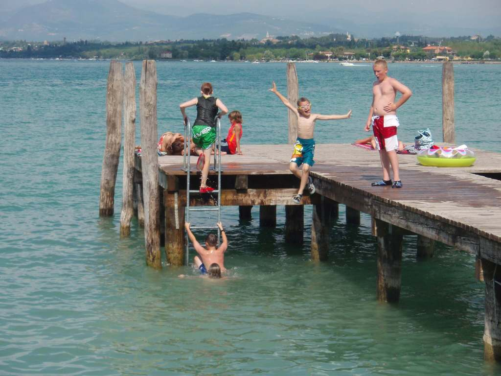 Boys jumping off a pier