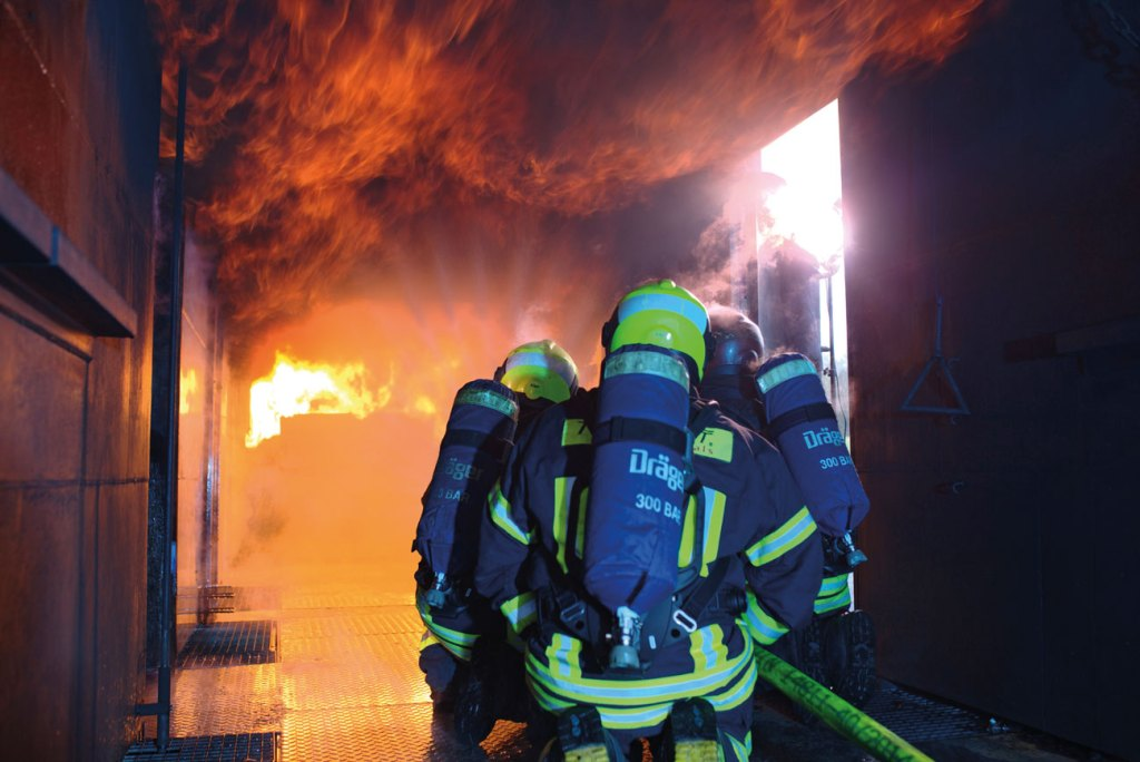 Firefighters tackling a fire in a Dräger hot fire training facility with Dräger firefighting equipment.