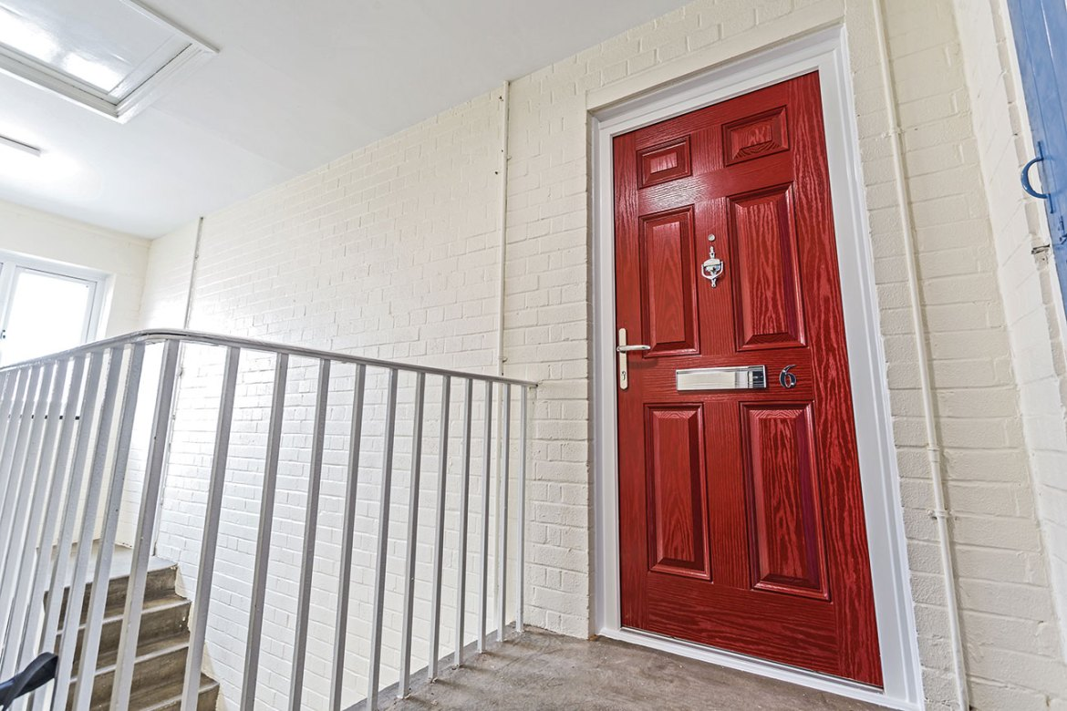 A solid (Neuma fds 68P) GRP composite fire entrance door in Red, installed in a block of flats managed by an Arm's Length Management Organisation (ALMO) in the west of England.