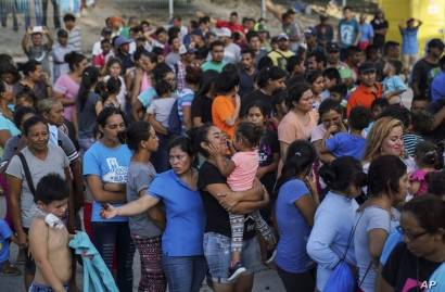 """In this Aug. 30, 2019, photo, migrants, many who were returned to Mexico under the Trump administration's """"Remain in Mexico,"""" program wait in line to get a meal in an encampment near the Gateway International Bridge in Matamoros. Many shelters at…"""