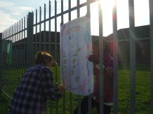 "The last job of the day, as the sun sets lazily, is to put all the Peace Day posters, full of information about human rights and encouraging others to practise Peace Day every day, on the Joza Youth Hub fence. As they work, the awarenet volunteers murmur about the sad stories they've heard that day, and how it's a good thing that their eyes are remaining open. ""Looking is the first step to moving to change,"" says volunteer Mcvay Bako. Photo by: Dani Kreusch."