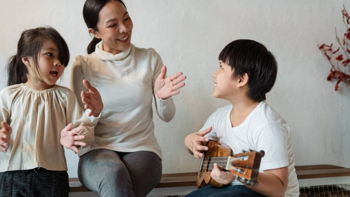 ethnic boy playing ukulele for cheerful sibling and mother