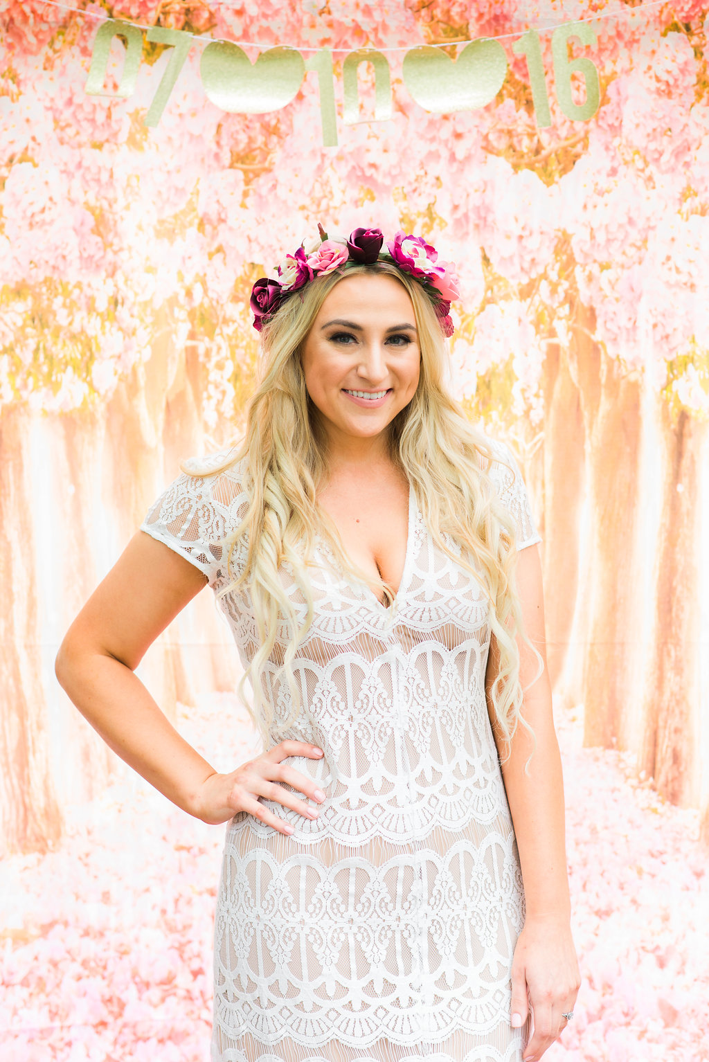 garden bridal shower photo booth with the bride in a stunning lace bridal shower dress and