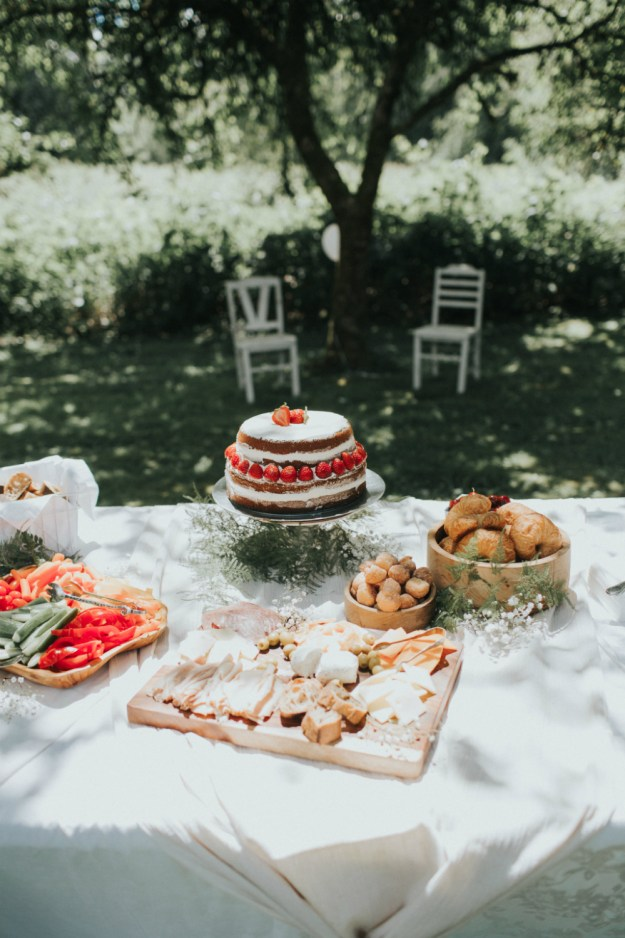 Garden party spread with a naked cake decorated with strawberries and cream. A Bohemian Bridal Shower in the Garden | Ultimate Bridesmaid | Alyssa Wilcox Photography