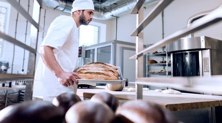 Padeiro preparando pães com equipamentos de padaria