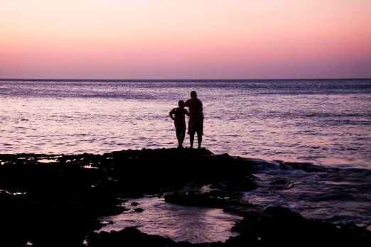 father and child near on body of water during sunset