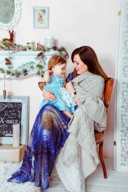 woman in blue white and brown dress holding baby in teal dress inside house