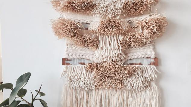 image of woven tapestry hanging on white wall behind a plant