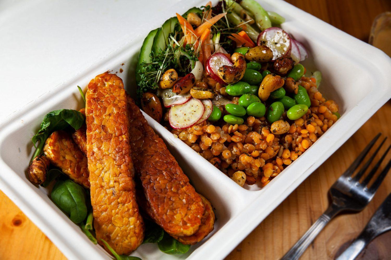 Lupinentempeh in einer Bowl zu buntem Salat mit Gemüsestreifen, Linsen, Bohnen, gerösteten Nüssen und dazu eine Kichererbsensauce. In der Togo-Box vom Fela.