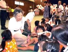 地震被害が出た伊豆諸島の神津島を訪問し、子どもたちにひざをついて話し掛けられる天皇、皇后両陛下2001年7月21日