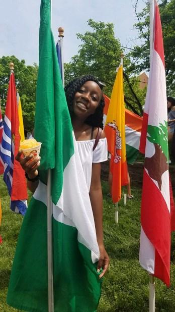 Freshman Kathryn Obisesan by the Nigerian flag on Hornbake Plaza. Photo Credit: Vanessa Barker