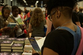 """College Park, Md. resident, Kelli Wade, 31, reads the inside cover of the 2015 coming-of-age novel """"All American Boys"""" by Jason Reynolds and Brendan Kiely at the 16th annual Library of Congress National Book Festival. Wade, who has always wanted to come to the festival, found herself at the Walter E. Washington Convention Center for the first time Saturday Sept. 24, 2016. (Jordan Stovka/Bloc Reporter)"""