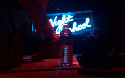 """Alan Palomo's feet never ceased movement as the Neon Indian frontman danced across the stage throughout the entirety of the set at 9:30 Club Friday, Oct. 7, 2016. The title of the group's third album, """"Night School,"""" is depicted on a neon sign in the background. (Jordan Stovka/Bloc Reporter)"""