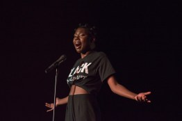 """Maud Acheampong, a freshman neurobiology and physiology major performs at Black Monologues in the Hoff Theatre. Acheampong read two poems entitled """"1856"""" and """"Crack,"""" the first of which tells the story of Margaret Garner from Garner's perspective after she was captured. (Cassie Osvatics/Bloc Reporter)"""
