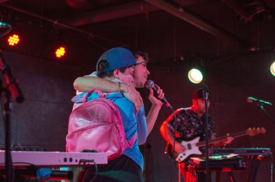 Lead singer of LA band Electric Guest, Asa Taccone, sings on stage with a fan during their performance at U Street Music Hall in D.C. Pictured in back is their touring bassist. (Cassie Osvatics/Bloc Reporter)