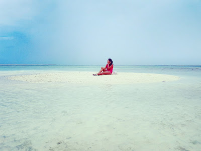 girl sitting in the middle of a tiny sandbank made by low tide
