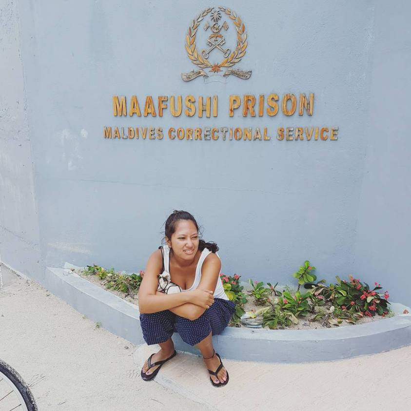 girl sitting in front of maafushi prison, looking distressed