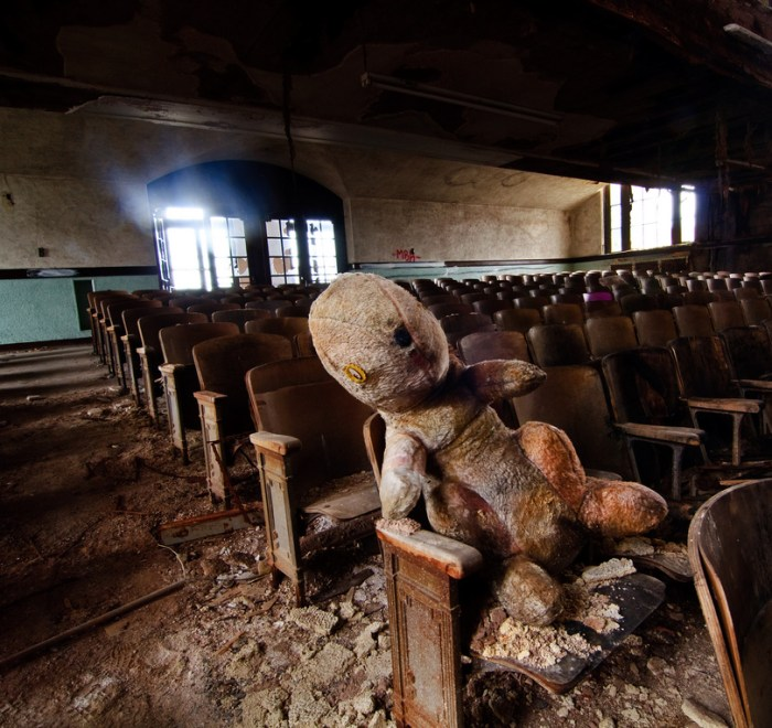 A photo of an old stuffed animal sitting in the audience of an abandoned theater by Colin Knowles on Flickr