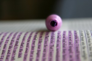 A photo of a pink highlighter on a book by Quinn Dombrowskion Flickr