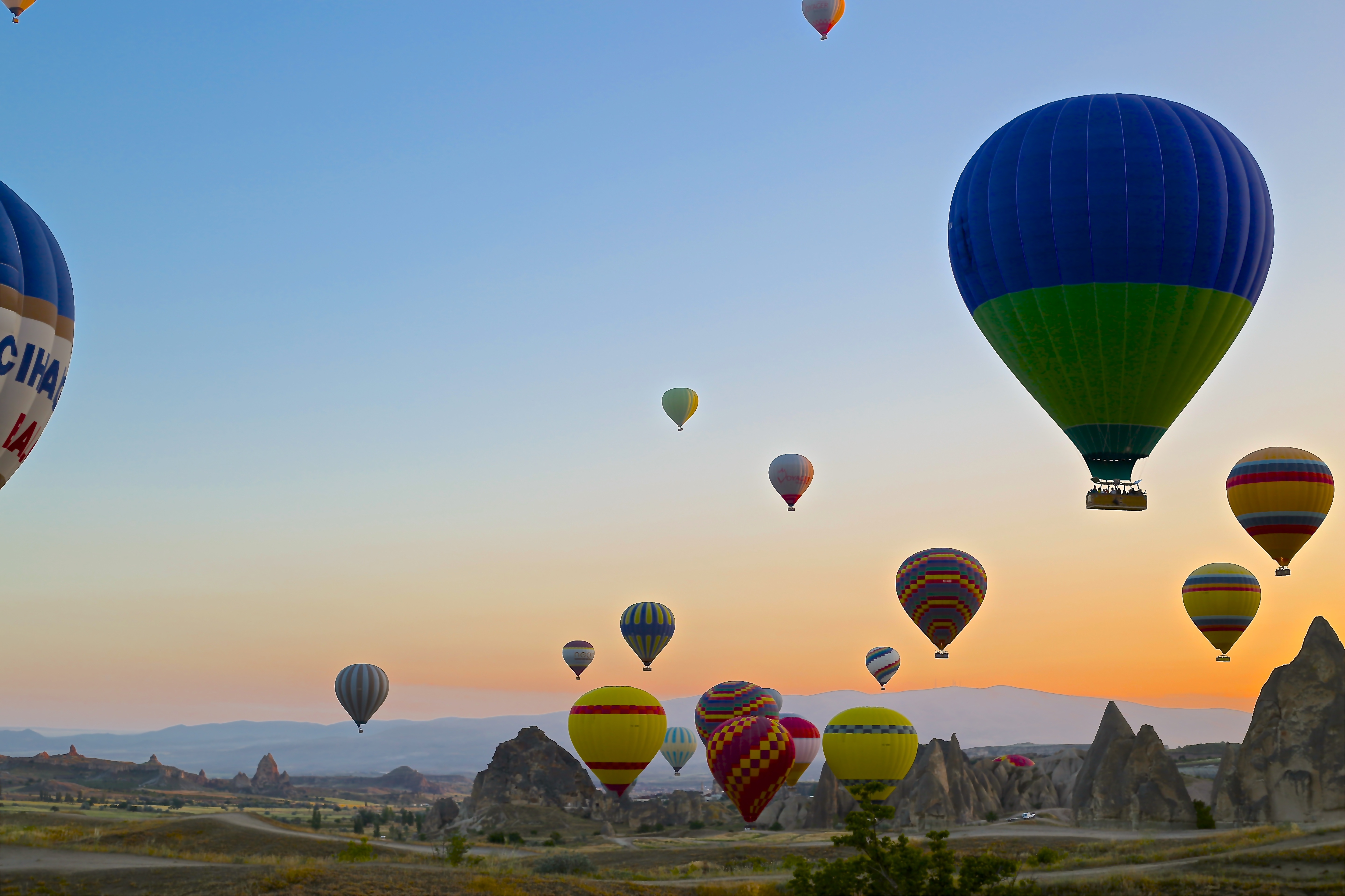 A bunch of hot balloons floating at sunset by Daniela Cuevas on Unsplash