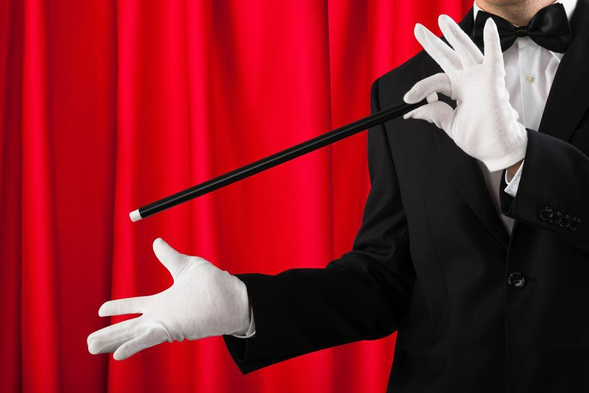 Close-up Of Magician In Suit Showing Trick With Magic Wand
