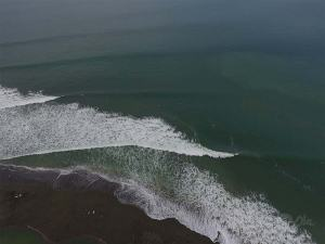 aerial view of waves breaking around point