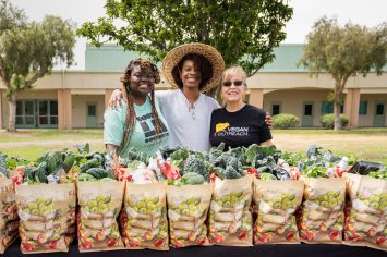 Gwenna Hunter, Avaion Ruth, and Kim King with Vegan Outreach stand in front of roughly 100 bags of fresh local produce given to local communities impacted by the COVID-19 crisis in Los Angeles. Photo by Nikki Ritcher / #unboundproject / We Animals Media.