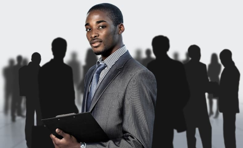 Home Page - An african man in a charcoal pin strip business suit and pinstripe shirt and tie holding a clipboard