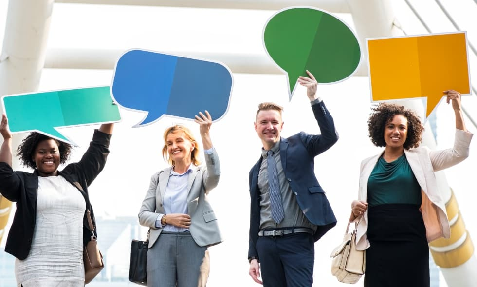 marketing page - image of four people holding speech bubble cutouts