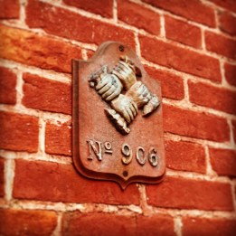 The four clasped hands is one of the earliest fire mark examples in the United States. The number listed below represents the policy number.