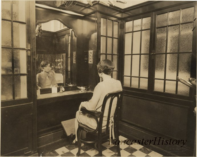 A woman checking out her new hairdo in the mirror of the salon at Watt and Shand.