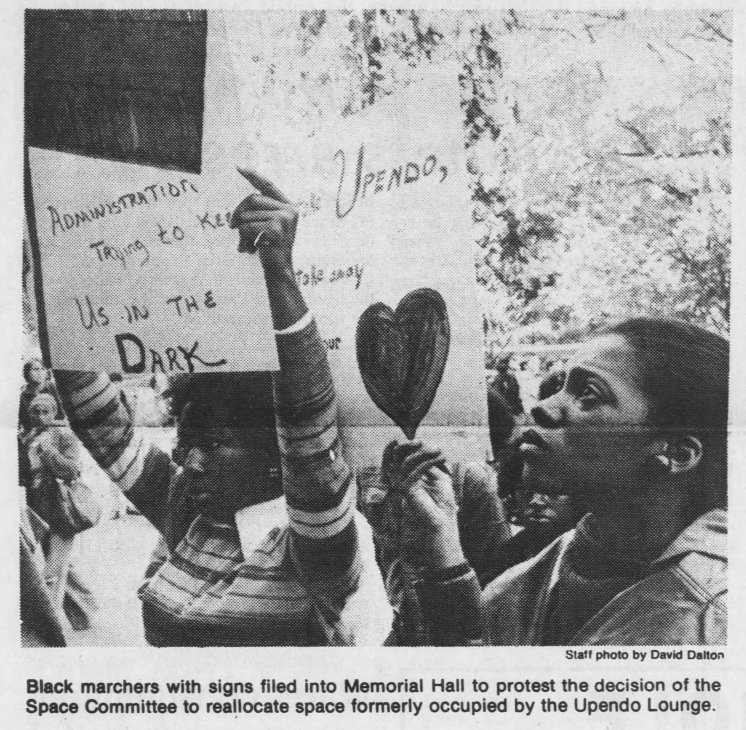 """""""Black marchers with signs filed into Memorial Hall to protest the decision of the Space Committee to reallocate space formerly occupied by Upendo Lounge."""" Photo by David Dalton inThe Daily Tar Heel, 13 October 1976, Page 1."""