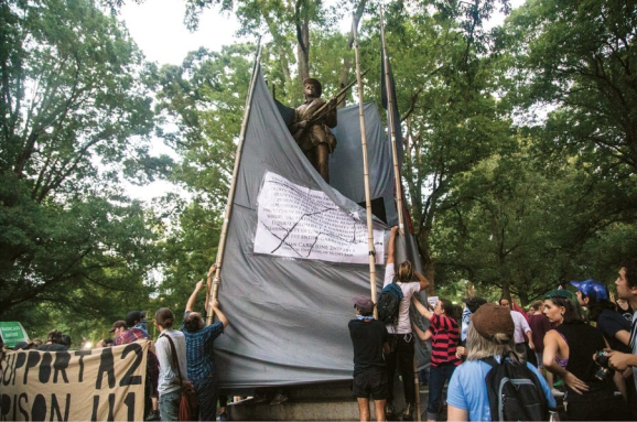 Banners Around Silent Sam, 20 August 2018, Photograph in the Carolina Alumni Review, September/October 2018, Page 38.