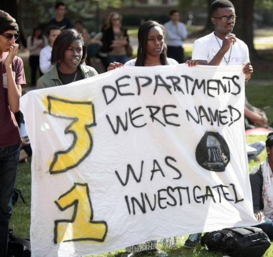"""Freshmen, from left, Tesarah Boyd, Jasmin Brooks and Adeyemi Olatunde hold a banner at the Wainstein Rally. Photo in Alexander, Johnathan, """"UNC students rally in support of African studies department,""""the Raleigh News and Observer, 29 October 2014."""