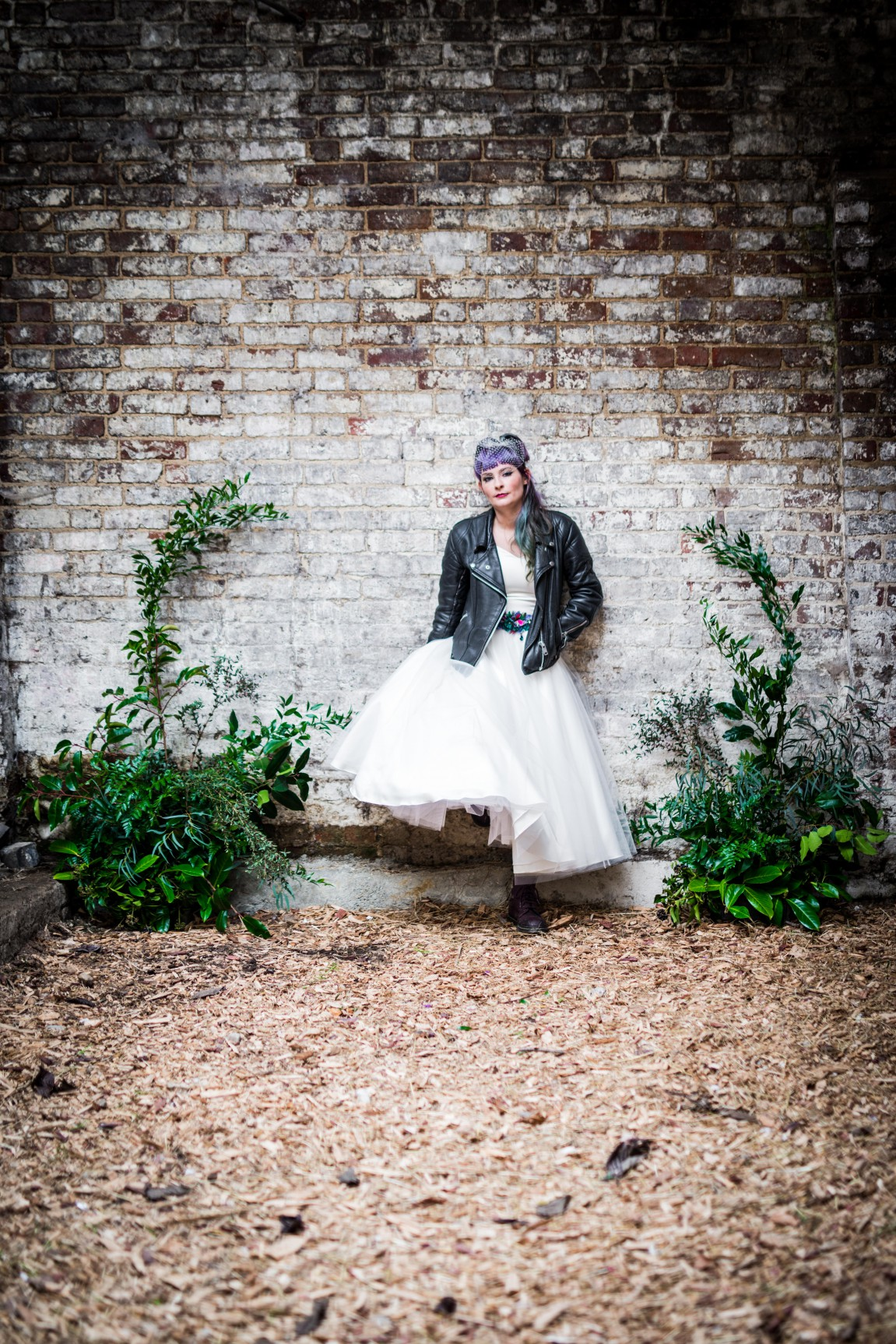 Peacock barns - alternative unconventional wedding photoshoot - rustic decadent - bride by barn wall