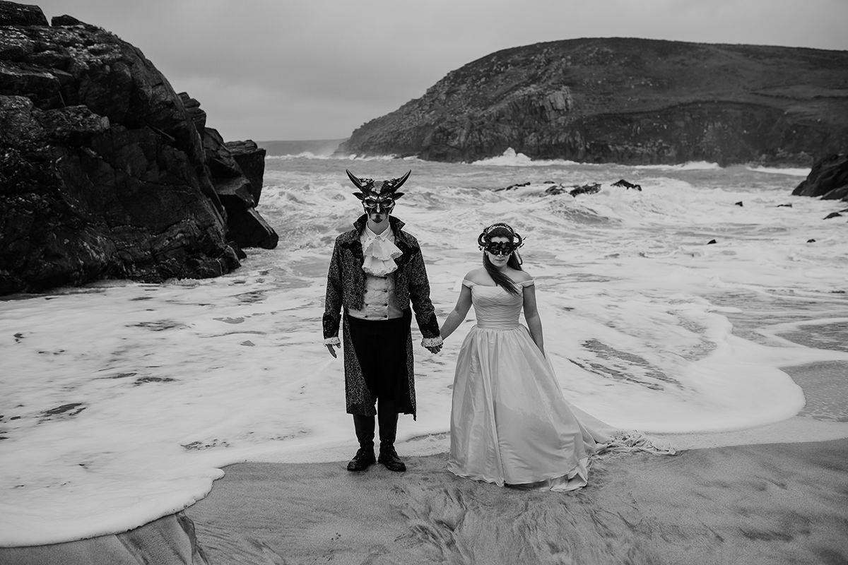 Black and white photo - Masquerade bride and groom wedding in the sea with crashing waves - Boho Cornwall wedding venue - Honeydew Moments Photography (41)