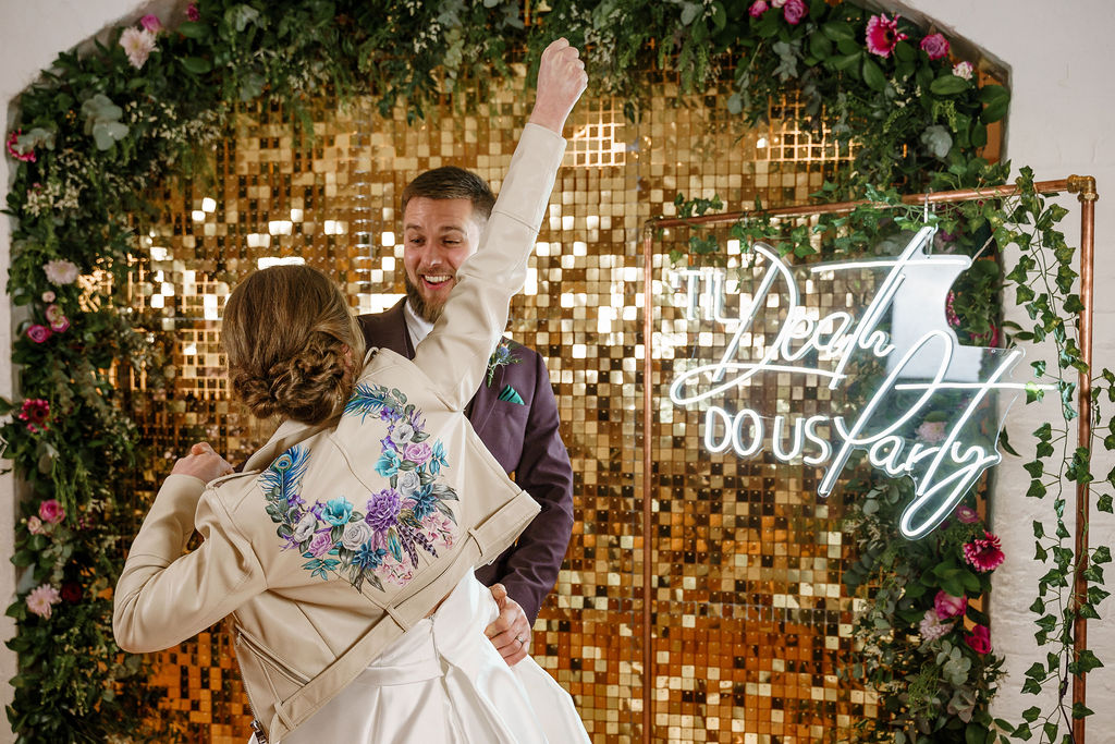 peacock themed wedding - peacock wedding - unique wedding colour scheme - quirky wedding - luxurious wedding - neon wedding sign - til death do us party - sparkly wedding backdrop- fun wedding- unique wedding leather jacket