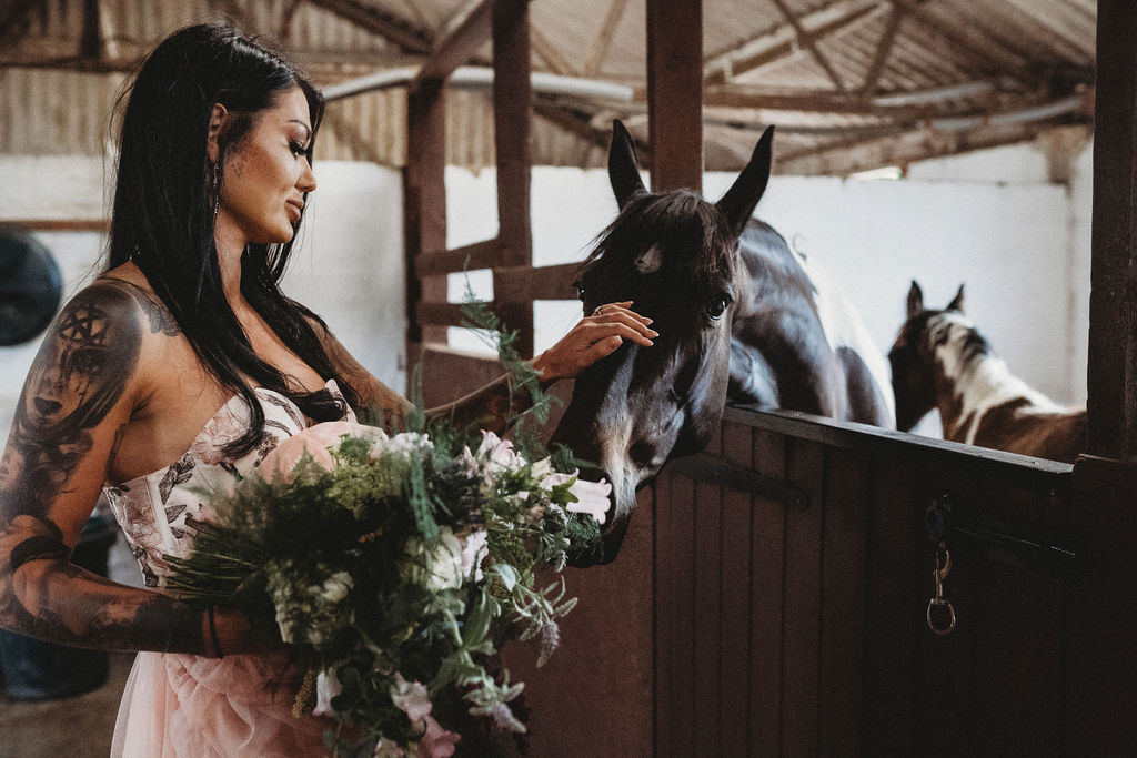 bride stroking a horse - alternative farm wedding, edgy wedding, tattooed wedding, alternative wedding