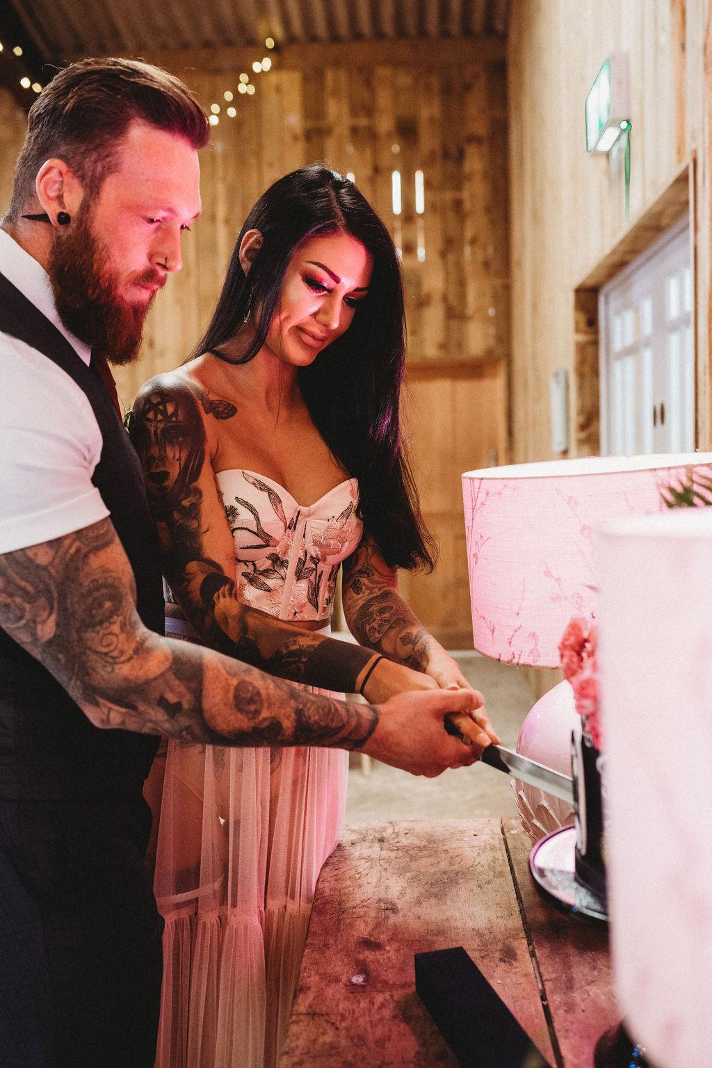 bride and groom cutting cake - alternative farm wedding, edgy wedding, tattooed wedding, alternative wedding