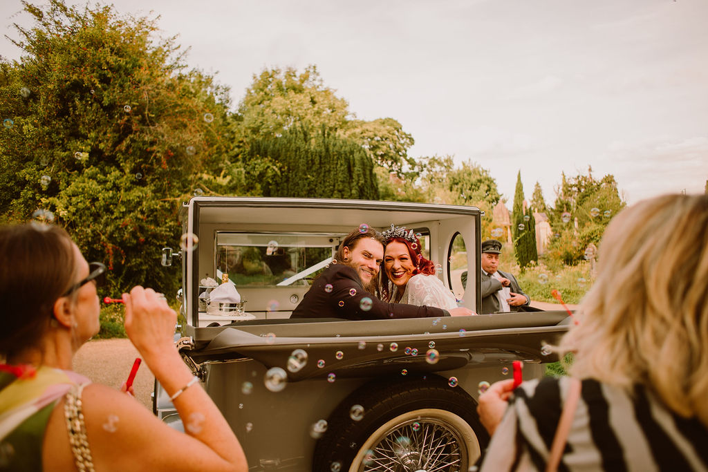 bride and groom in wedding car with bubbles