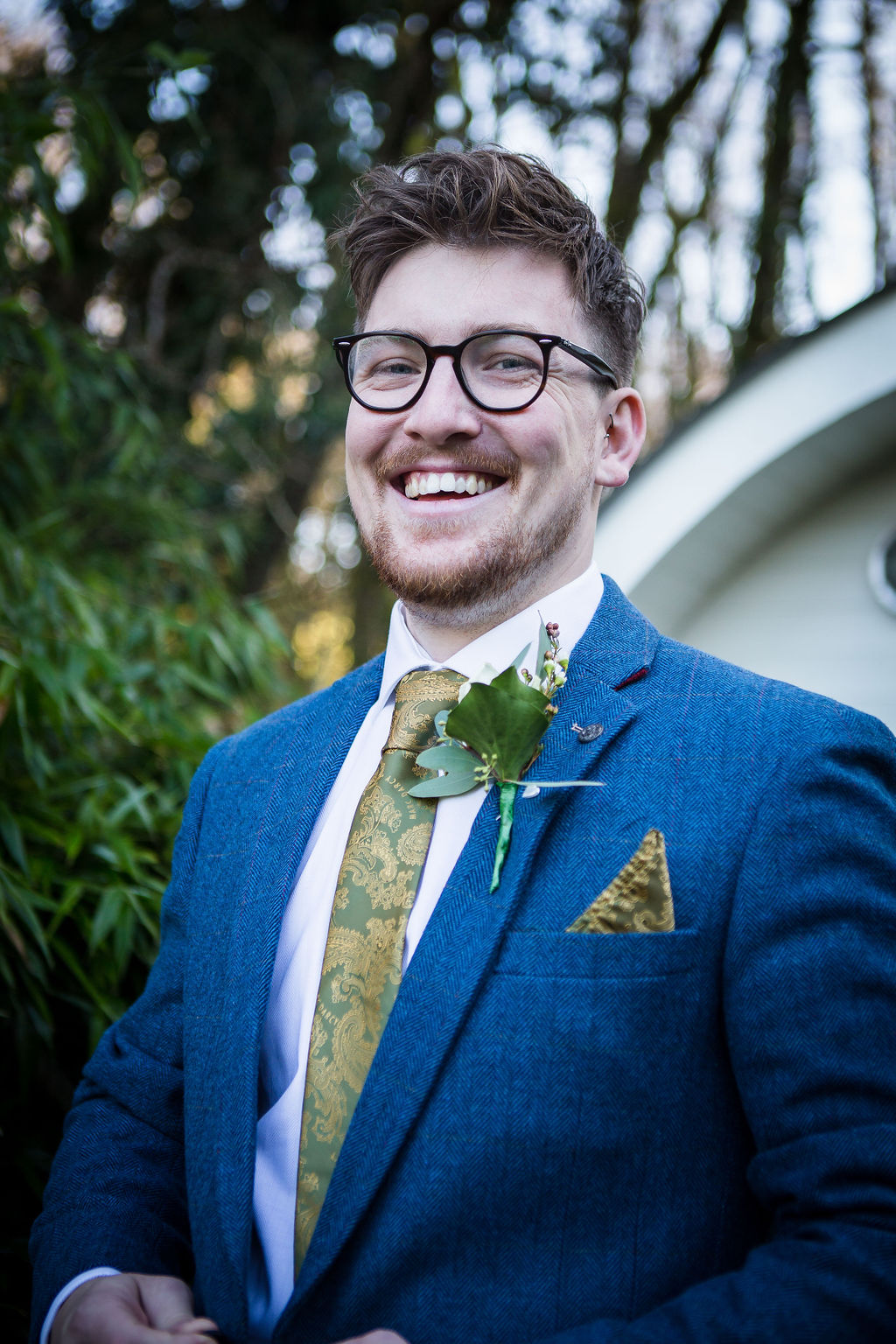 groom smiling - blue grooms suit with green tie