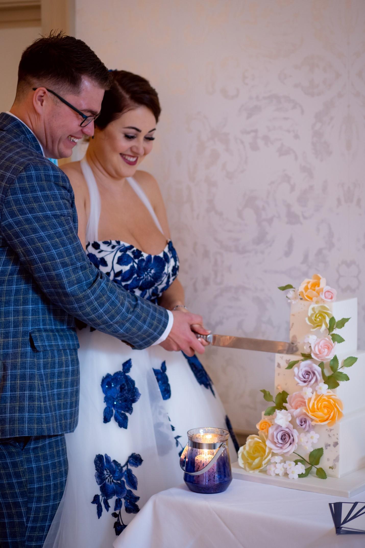 bride and groom cutting cake - blue wedding dress - unique wedding cake