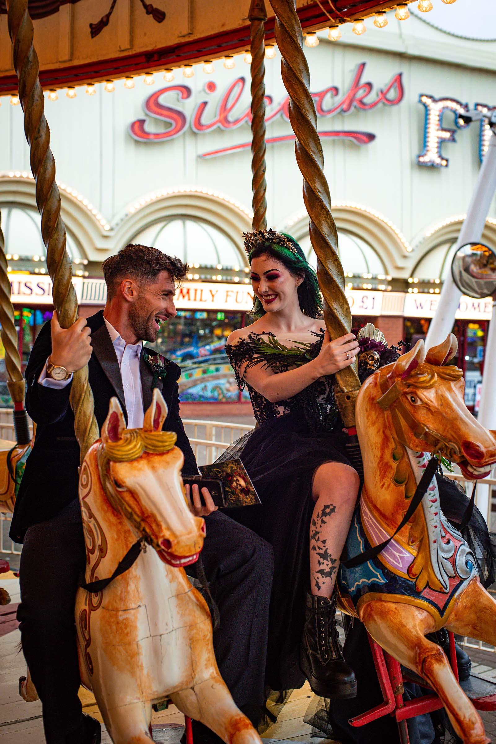 alternative luxe wedding - slytherin wedding - gothic wedding - alternative wedding - bride and groom on carousel - fairground wedding