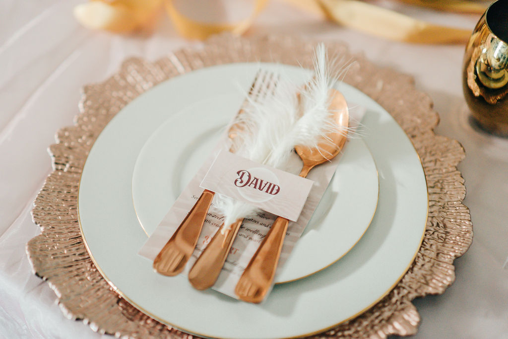 table place setting with gold charger plate, white feather and name tag