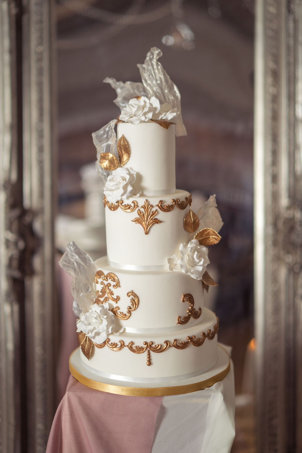 Ornate 3 tier gold and white wedding cake with white sugar flowers for movie themed wedding day on dusky pink pedestal