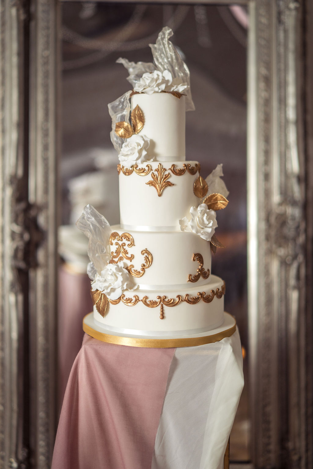 Ornate 3 tier gold and white wedding cake with white sugar flowers for movie themed wedding day on dusky pink pedestal 2