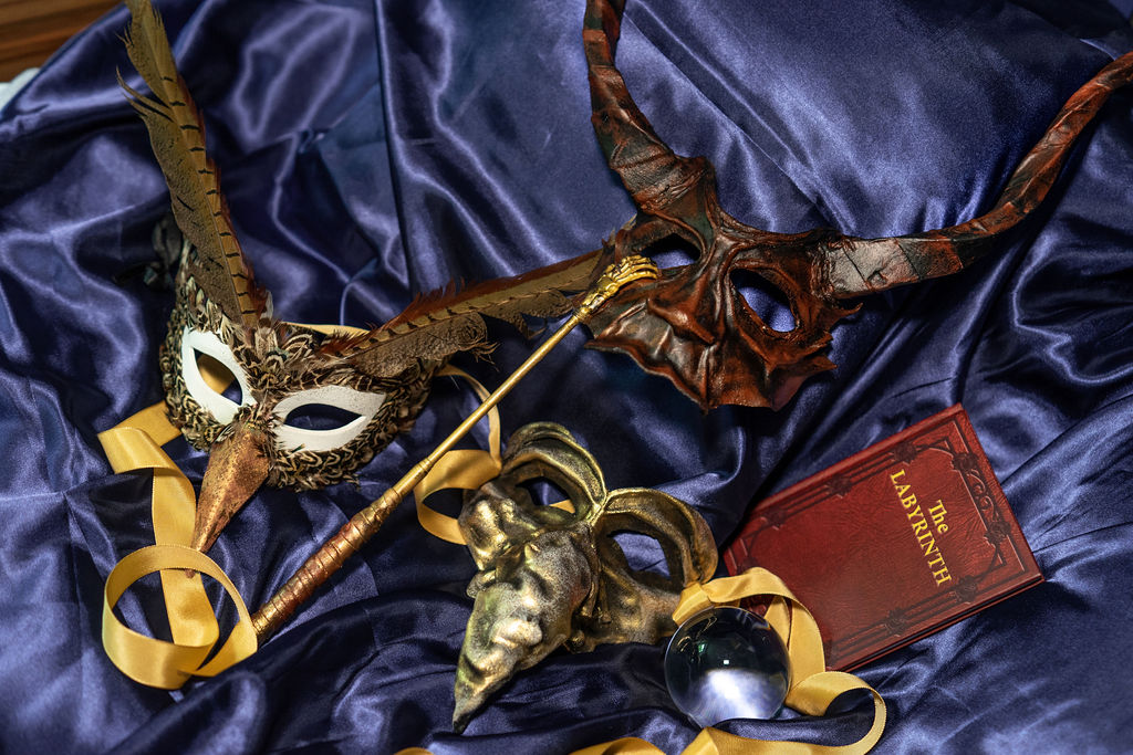 The Labyrinth book and various masks with gold ribbon & feathers on blue silk