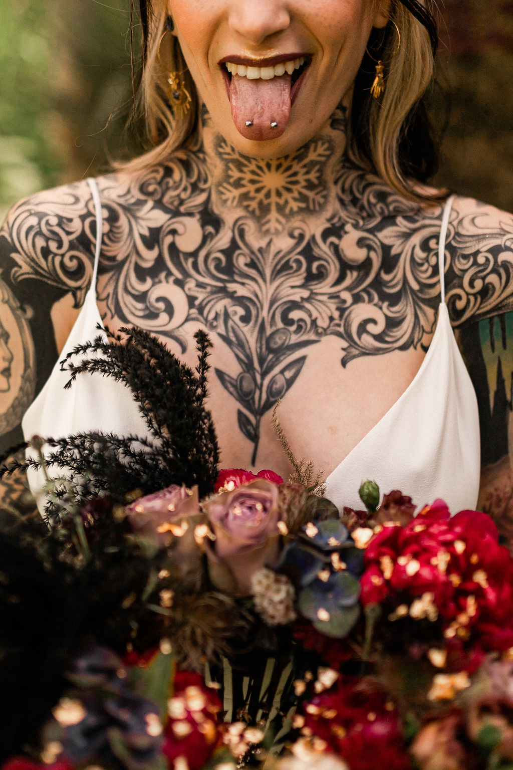 tattooed bride with tongue piercing and alternative wedding flowers