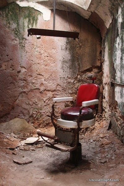 A barber's chair sits alone in a crumbling room at Eastern State Penitentiary in Philadelphia, Pennsylvania.