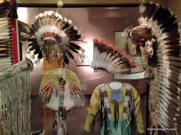 Native American headdresses and clothing on display while visiting the Carnegie Museum of Natural History.